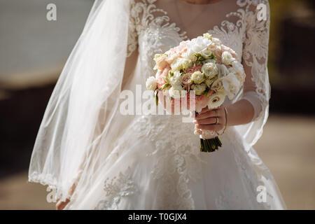 Junge schöne Mädchen in einem eleganten Kleid steht und die hand Bouquet von Pastell Blumen und Grün mit Schleife an der Natur. Die Braut hält einen Wir - Stockfoto