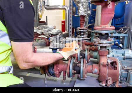 Mechanische Ingenieur in einer Gut sichtbare Sicherheitsweste arbeiten an einer Pumpe in einem Kesselraum eingestellt Stockfoto