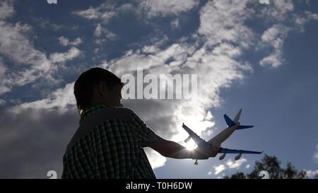 Jungen spielen mit Spielzeug Flugzeug gegen schönen Himmel - Stockfoto