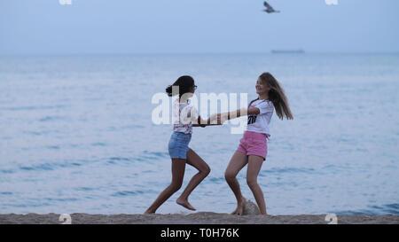 Zwei glückliche Mädchen Wirbeln am Strand in der Nähe vom Meer am Abend - Stockfoto