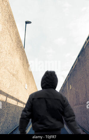 Rückansicht eines Silhouette Figur in einem Hoodie, zurück zu Kamera, die sich aus einer Unterführung und entfernt auf einer Steigung - Stockfoto