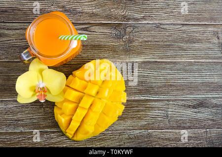 Mango Smoothie in einem Glas und frischer Mango auf einer hölzernen Hintergrund. Mango schütteln. Tropische Früchte Konzept. Ansicht von oben, kopieren Raum - Stockfoto