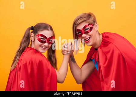 Mutter und Tochter gekleidet wie Superhelden spielen Arm Wrestling, und wenn man die Kamera auf gelben Hintergrund. Super Mom. Super Tochter. Roten Cape. Rote Maske. Parenting. - Stockfoto