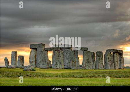 Grossbritannien, England, Wiltshire. Stonehenge unter stürmischen Himmel bei Sonnenuntergang. - Stockfoto