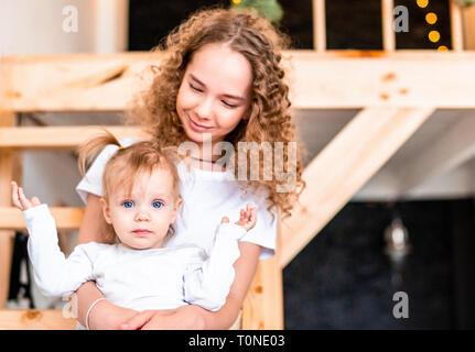 Ältere Schwester umarmen und sitzen auf Treppe mit jüngeren Schwester. Kleinkind mit Unterhaltung und lassen Sie sich überraschen. Familie Liebe und Unterstützung. - Stockfoto
