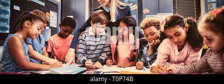 Lehrer Schulmädchen bei ihren Hausaufgaben im Klassenzimmer helfen