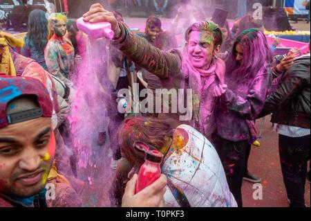 Ein Mann wird gesehen, werfen farbigen Pulvern bis zu einer Frau. Millionen von Menschen auf der ganzen Welt feiern die jährliche Holi Hangámá Festival, auch als das Fest der Farben genannt. Für die Hindus ist es eine Feier der Ankunft des Frühlings, das Neue Jahr und Sieg in einem. Den größten indischen Bevölkerung in Europa (außerhalb des UK) können in Den Haag, gefunden werden Dies ist einer der größten in Europa. Das Highlight der Holi Feiern ist der Umzug durch die multikulturellen Transvaal und Schilderswijk Nachbarschaften. Die Teilnehmer an der Prozession werfen Bunte Pulver an sich selbst und an ea - Stockfoto