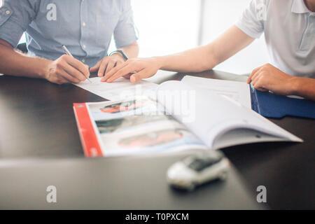 Zwei Männer sitzen am Tisch. Kerl auf der linken Unterzeichnung Papiere, während man auf der linken Seite weist mit der Hand. Es ist geöffnet Journal vor Ihnen. Auch gibt es kleine whi - Stockfoto