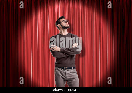 Junger Mann mit Brille legere Kleidung auf rote Bühnenvorhänge Hintergrund - Stockfoto