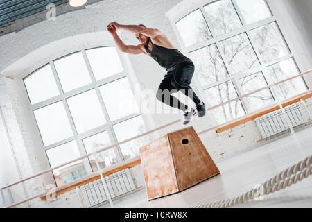 Dynamische schuss Fitness männlichen Athleten springen im Quadrat in der Turnhalle. Starke Mann, springen auf hölzernen Hocke Kasten an hellen Saal - Stockfoto