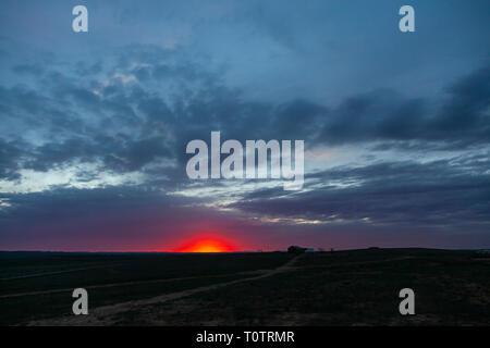 Sonnenaufgang über dem Gegentala Grasland nördlich von Hohhot, Innere Mongolei, China. Ein einsames Haus mit einer Jurte (Ger) auf den weiten Ebenen. - Stockfoto