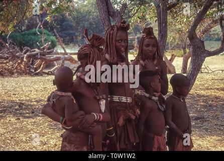 Gruppe von jungen Frauen und Kindern der Himba ethnische Gruppe in der Nähe der Epupa Wasserfälle auf dem Kunene Fluss in Namibia, Grenze zu Angola - Stockfoto