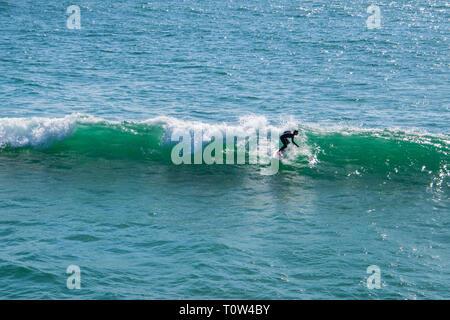 Huntington Beach, Kalifornien - 11. Oktober 2018: ein Surfer in einen Taucheranzug gesehen Balancing auf seinem Surfbrett beim Reiten eine kleine Welle in der Blauen gree - Stockfoto