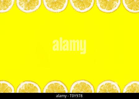 Muster aus frischen Zitronenscheiben auf gelbem Hintergrund mit Kopie Raum in der Mitte. Ansicht von oben, flatlay. Obst Hintergrund. - Stockfoto