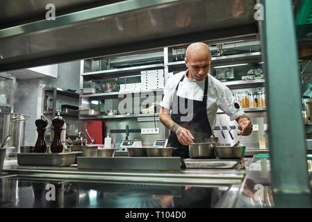 Restaurant Chef. Konzentrierten jungen Koch in schwarze Schürze ist Kochen in seinem modernen Restaurant Küche. Kochen Konzept - Stockfoto