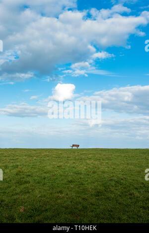 Leere Sitzbank, weiße Wolken und blauer Himmel oben am Grünen Hügel. - Stockfoto