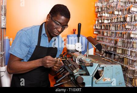 Erfahrene Schlosser arbeiten an wichtigen duplizieren Maschine in Workshop fokussiert - Stockfoto