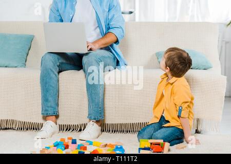 Vater saß auf der Couch und mit Laptop während Vorschüler Sohn spielen mit bunten Bausteinen zu Hause - Stockfoto