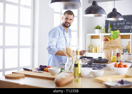 Lächelnd und selbstbewusst Koch stehen in großen Küche - Stockfoto