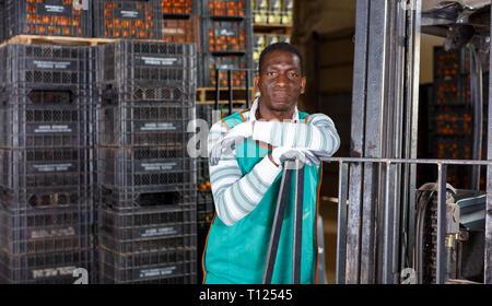 Nach afrikanischen Arbeiter- und E-Stapler im Lager mit Behältern von Mandarinen - Stockfoto