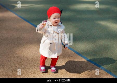 Süße blonde kleine kleinkind Mädchen in schönen beigefarbenen Trenchcoat und roter Kappe im Freien an Spielplatz spielt - Stockfoto