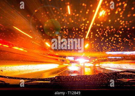 Auto schnell Nacht Licht Unschärfe regnet Fahrers aus der Konsole Armaturenbrett. - Stockfoto