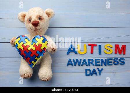 Welt Autismus Bewußtsein Tag, psychische Gesundheit Konzept mit Teddybär holding Puzzle oder Stichsäge Muster auf Herz - Stockfoto