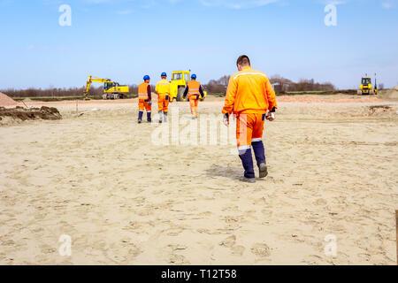 Die Bauarbeiter werden zu ihrem Arbeitsplatz nach einer Pause an der Baustelle. - Stockfoto