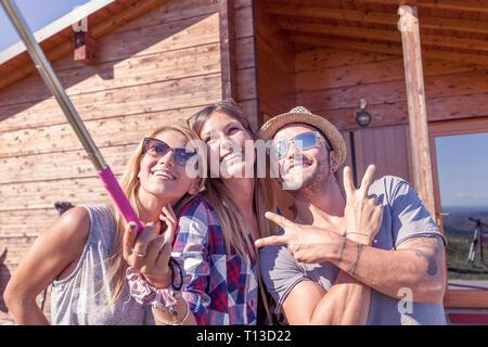 Gruppe von lächelnden Freunde unter Lustig selfie mit Smart Phone auf einem Vintage warmer Farbe gefiltert suchen - Stockfoto