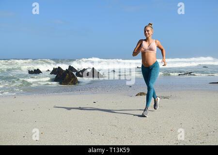 Lächelnd schwangere Frau Jogging am Strand - Stockfoto