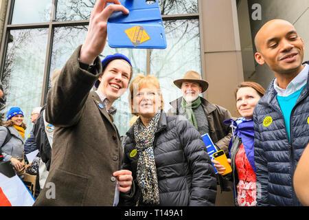 """London, UK, 23. März 2019. Eine Demonstrantin nimmt selfies mit Demonstranten in farbenfrohe Outfits mit Plakaten und Bannern. Die Demonstranten aus ganz Großbritannien und viele britische Ex-Pats aus dem Ausland, haben reiste in die 'Abstimmung März"""", auch """"unter die Leute"""" März gelegt. Der März, durch Hunderte von Tausenden besucht, macht seinen Weg von Park Lane, Piccadilly, Trafalgar Square und Whitehall mit Reden von Aktivisten und Politiker im Parlament Square, Westminster zu beenden. - Stockfoto"""