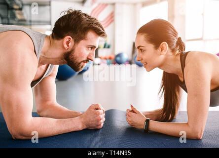 Der Trainer und sein Schüler tun plank Übung zusammen zur gleichen Zeit. Sie sind auf Training konzentriert und an jedem anderen suchen. Schnitt - Stockfoto