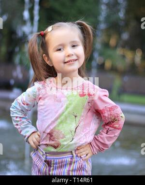 Portrait von glücklichen kleinen Mädchen in der Nähe von Brunnen im Stadtpark - Stockfoto