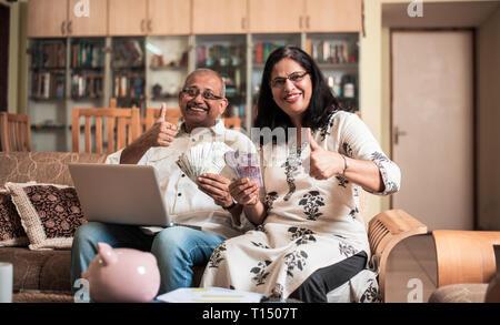 Ältere indische/asiatische Paar Buchhaltung, zu Hause finanzieren und Rechnungen mit Laptop, Rechner und Geld zu überprüfen, während auf Sofa/Couch zu Hause sitzen