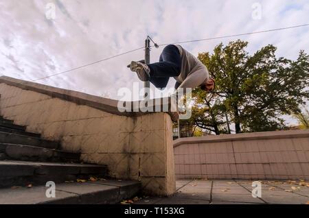 Ein junger Kerl führt einen Sprung durch den Beton Brüstung. Der Athlet Praktiken Parkour, Ausbildung in der Straße. Das Konzept der Sport subcultu - Stockfoto
