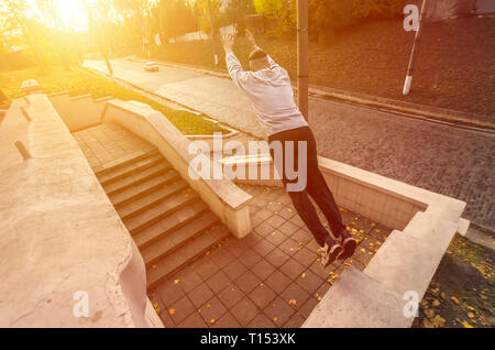 Ein junger Kerl führt einen Sprung durch den Raum zwischen dem konkreten Brüstungen. Der Athlet Praktiken Parkour, Ausbildung in der Straße. Das Konzept - Stockfoto