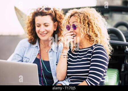 Paar von geschweiften schöne junge Frauen haben Spaß Lachen mit einem Laptop im Freien - technoogy und Personen Konzept - lustige Sachen für hübsche Frauen - Laug - Stockfoto