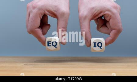 """Symbol für die Balance zwischen emotionaler Intelligenz und die Intelligenz Quotient. Hände halten zwei Würfel mit den Buchstaben """"EQ"""" und """"IQ"""" in Fron - Stockfoto"""