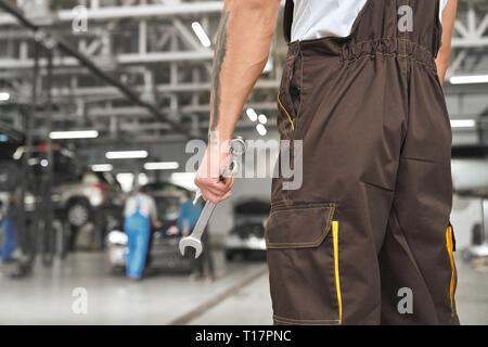 Rückansicht der Mechaniker im Autoservice, Schlüssel, Werkzeug zur Befestigung von Automobilen. Handwerker in Braun tragen Overalls, Uniformen. - Stockfoto
