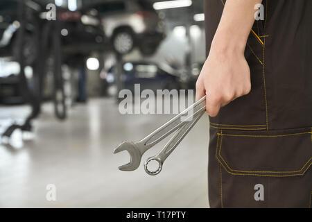 Nahaufnahme von Mechaniker hand Schlüssel, Spezialwerkzeuge für die Reparatur und zur Festsetzung von Fahrzeugen. Mann in Overalls in Autoservice. - Stockfoto