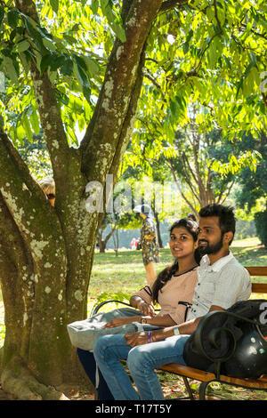 Junges Paar siiting auf einer Bank in der Königlichen Botanischen Garten von Peradeniya in der Nähe von Kandy, Sri Lanka - Stockfoto