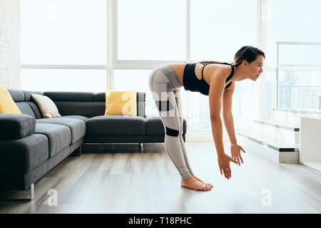 Frau zu Hause Praktizieren von Yoga Sonnengruß Routine - Stockfoto