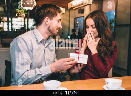 Kerl ist mit seiner Freundin ein Geschenk in das weiße Feld. Sie gehen davon aus, dass nicht. Er mag seine geliebte Frau glücklich zu machen. - Stockfoto