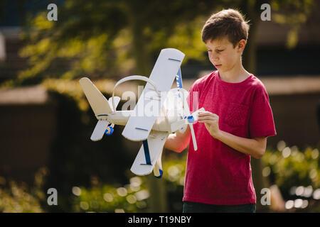 Junge spielt mit einem Spielzeug Flugzeug im Freien. Jugendliche junge Blick auf das Spielzeug Flugzeug in seine Hände im Freien. - Stockfoto