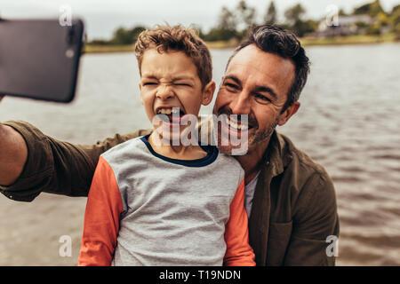 Nahaufnahme von Vater und Sohn eine selfie in der Nähe von einem See. Glückliches Kind Gesichter machen seine Zunge heraus, während sein Vater nimmt eine selfie. - Stockfoto