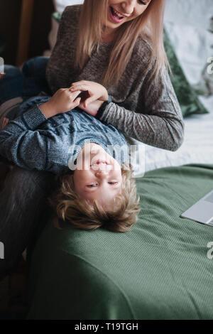 Freundliche kleine Junge Spaß mit Mutter auf dem Sofa Stockfoto