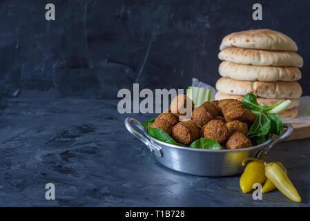 Falafelkugeln mit Fladenbrot, traditionellen israelischen oder im Nahen und Mittleren Osten Essen auf schwarzem Hintergrund - Stockfoto