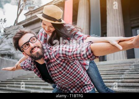 Verspieltes paar Touristen an Treppen. Bärtiger junger Mann hält Frau auf der Rückseite. Sie schauen sich an und halten Sie Ihre Hände seitlich vom Körper. - Stockfoto