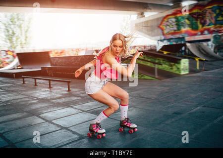 Schöne blonde Mädchen ist dabei einige Tricks beim Inlineskaten. Sie steht in einer untersetzten Position und nach unten schauen. Ihre Hände sind abgesehen von Körper - Stockfoto