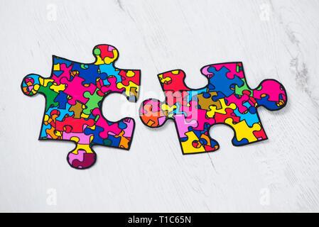 Zwei Puzzleteile mit vielen Puzzleteilen in verschiedenen Farben, Symbol der autism Bewußtsein, auf weißem Hintergrund rusitc Holzmöbeln gemusterten - Stockfoto